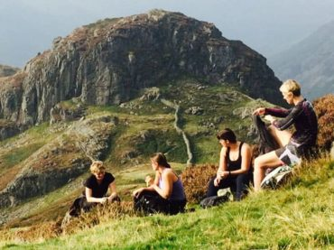 4 people sta relaxing backdrop mountains lake district