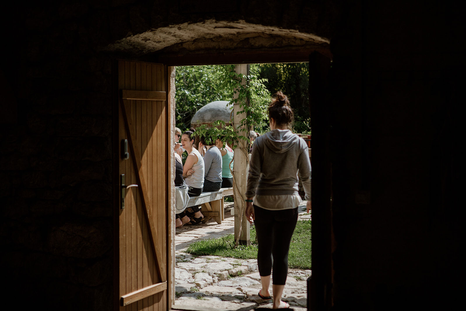 person walking out door to people seated outside - hiking yoga holiday montenegro
