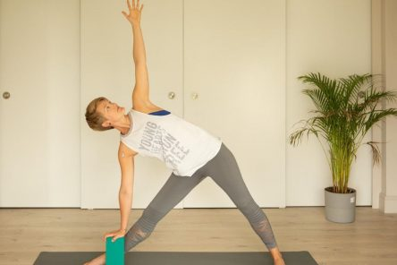 triangle yoga pose with brick self-limiting beliefs in yoga practice