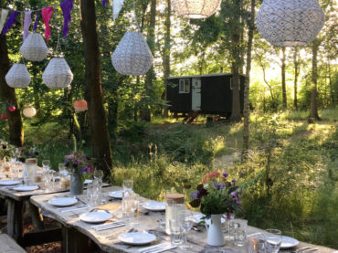 outdoor table laid and shepherds hut in woods